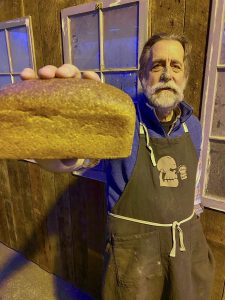 Bearded man in apron holds a loaf of bread in outstretched hand.