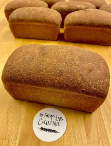 Unsliced loaves of fresh bread with a The Bread Lab Collective coaster.