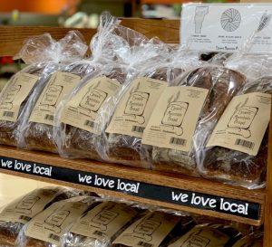 Shelf full of bagged sliced bread loaves.