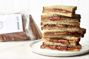 Plate of stacked PBJ sandwiches, open bag of bread in background