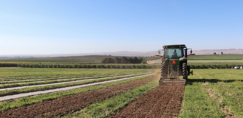 image shows a tractor pulling a rototiller attachment making individual tilled rows.