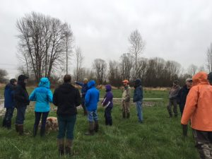 A group of people dressed in rain gear stands in a farmer's field, listening to the farmer.