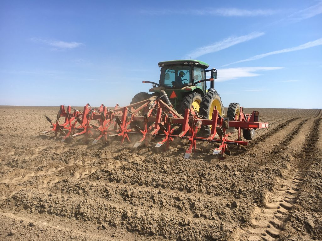 large equipment pulled by tractor through soil in field