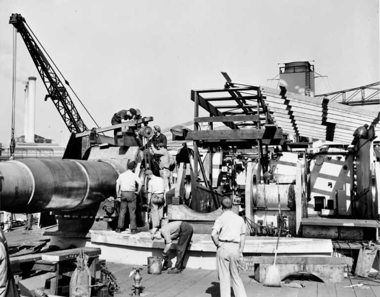 USS Iowa's forward Main Deck - shipyard workers install one of the 16 inch Mark 7 gun barrels in Turret 1. Fall 1942 - 80-G-K-507 picture number 1