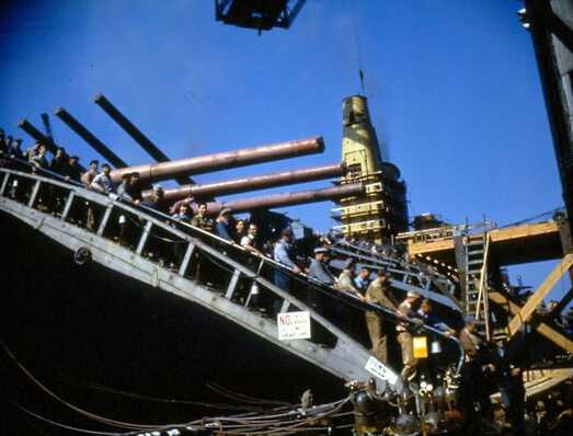 Shipyard workers departing IOWA from the forward gangway. Turrets 1 & 2's guns have been installed. Oct 1942 - 80-G-K-517 picture number 1