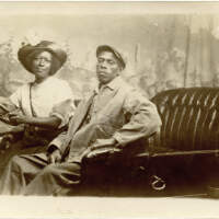 2020.399.001 Recto; Black and white postcard featuring an African American man and woman posing in an early motorcar, in front of a painted backdrop