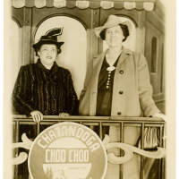 2020.181.001 Recto; Black and white photograph postcard showing two women posing in front of a prop train car