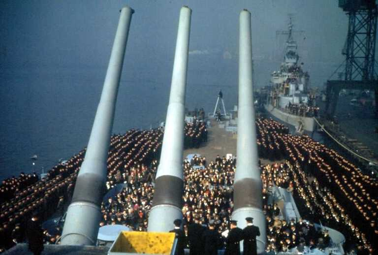 Looking aft - IOWA's crew rings the guests seated in the center. Destroyer astern appears to be USS Wainwright DD-419. 80-G-K-823 picture number 1