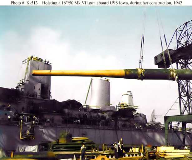 A crane hosts a 16 inch gun barrel onto IOWA for installation. Note the two stacks in the background. Fall 1942 - 80-G-K-513 picture number 1