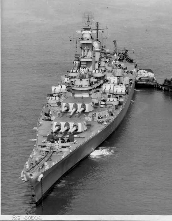 Bow view of USS Iowa anchored off New York with a trash barge placed at her port. April 7, 1943 - US Navy photo. picture number 1