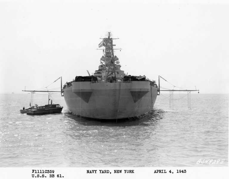 Stern view of USS Iowa anchored off New York with boat booms rigged. April 4, 1943 - F1111C359. picture number 1