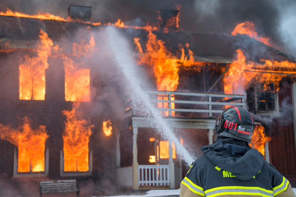 Firefighter extinguishing a structure fire