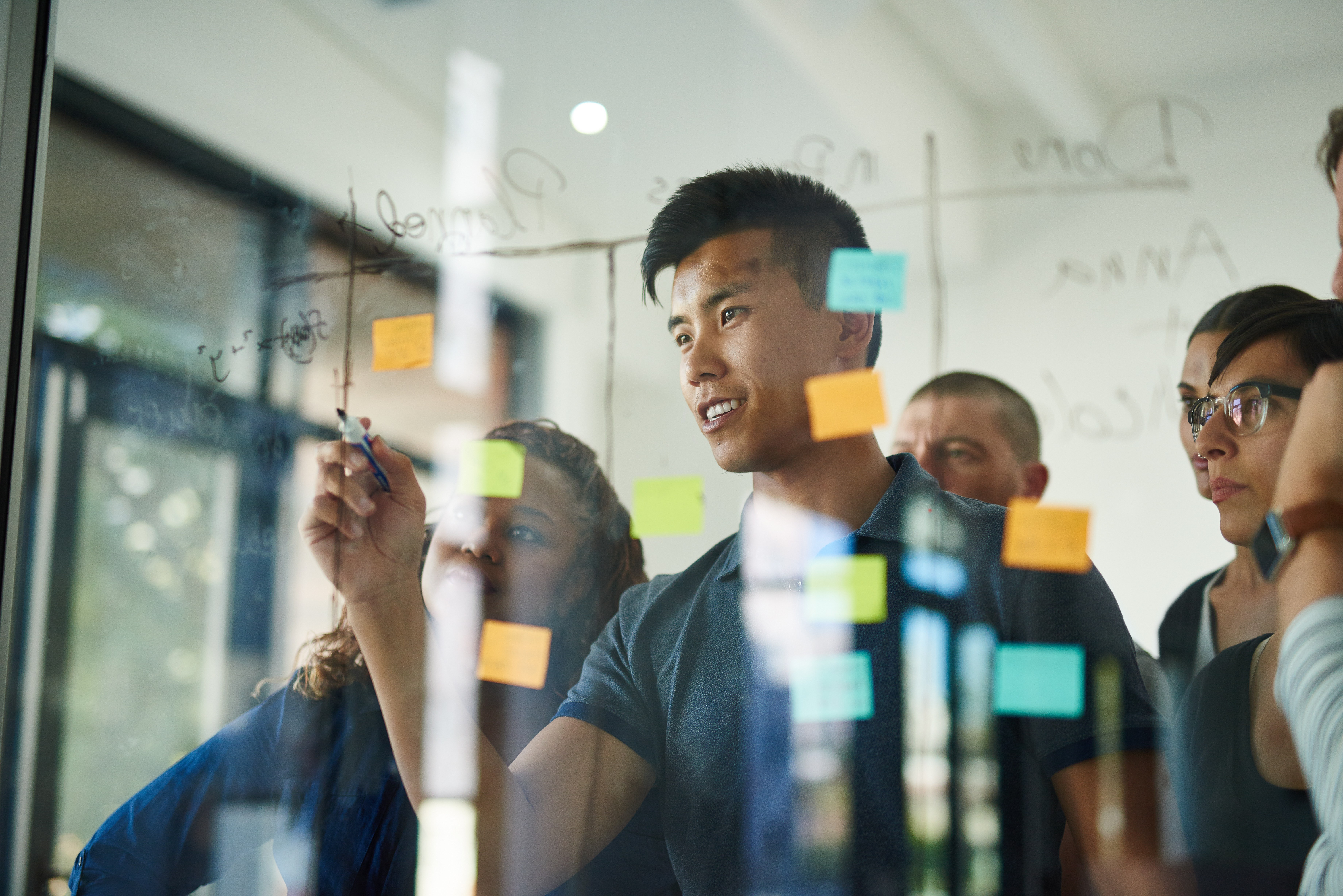 People collaborating in office using sticky notes