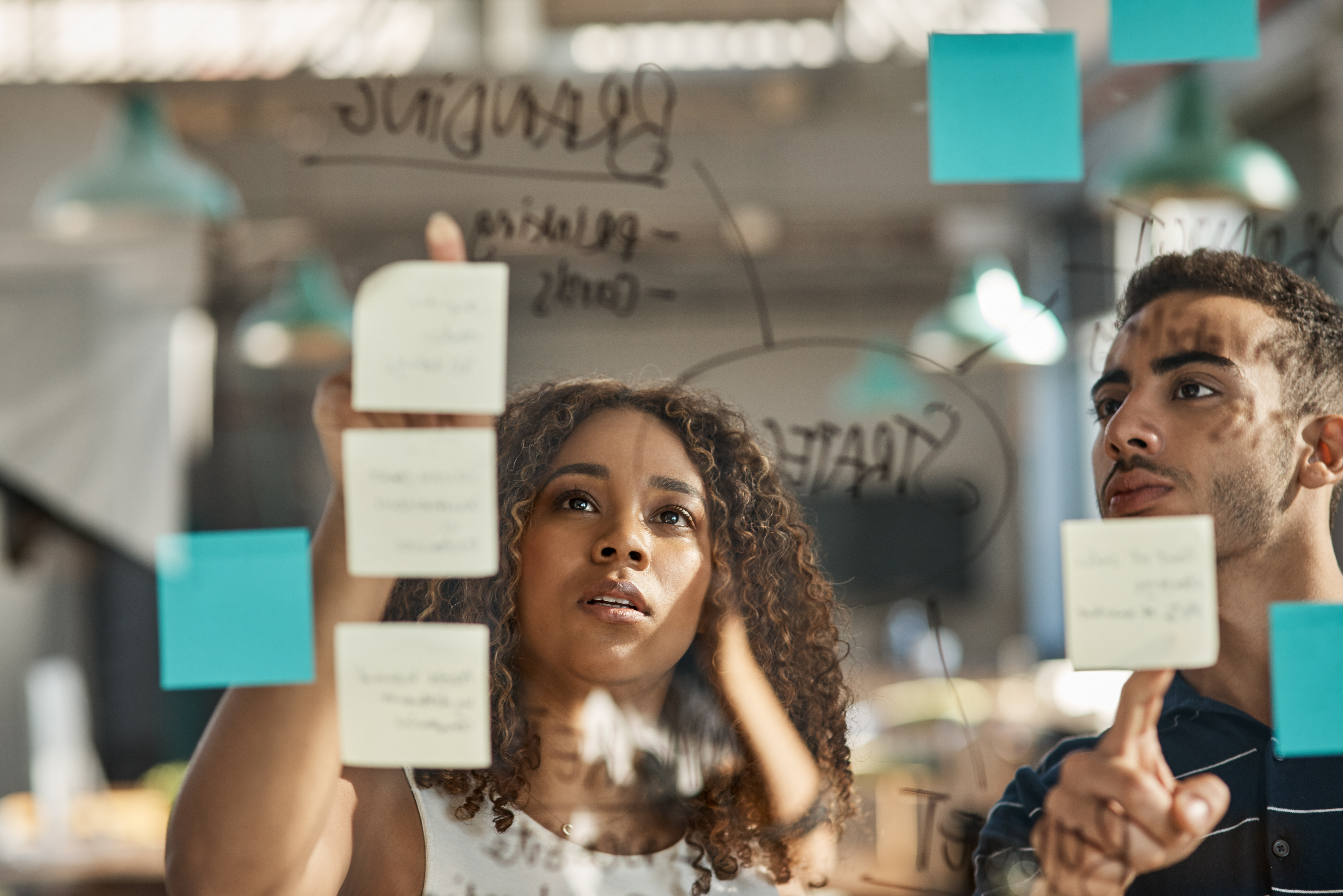 Man and woman in office collaborating on project by using sticky notes on a screen