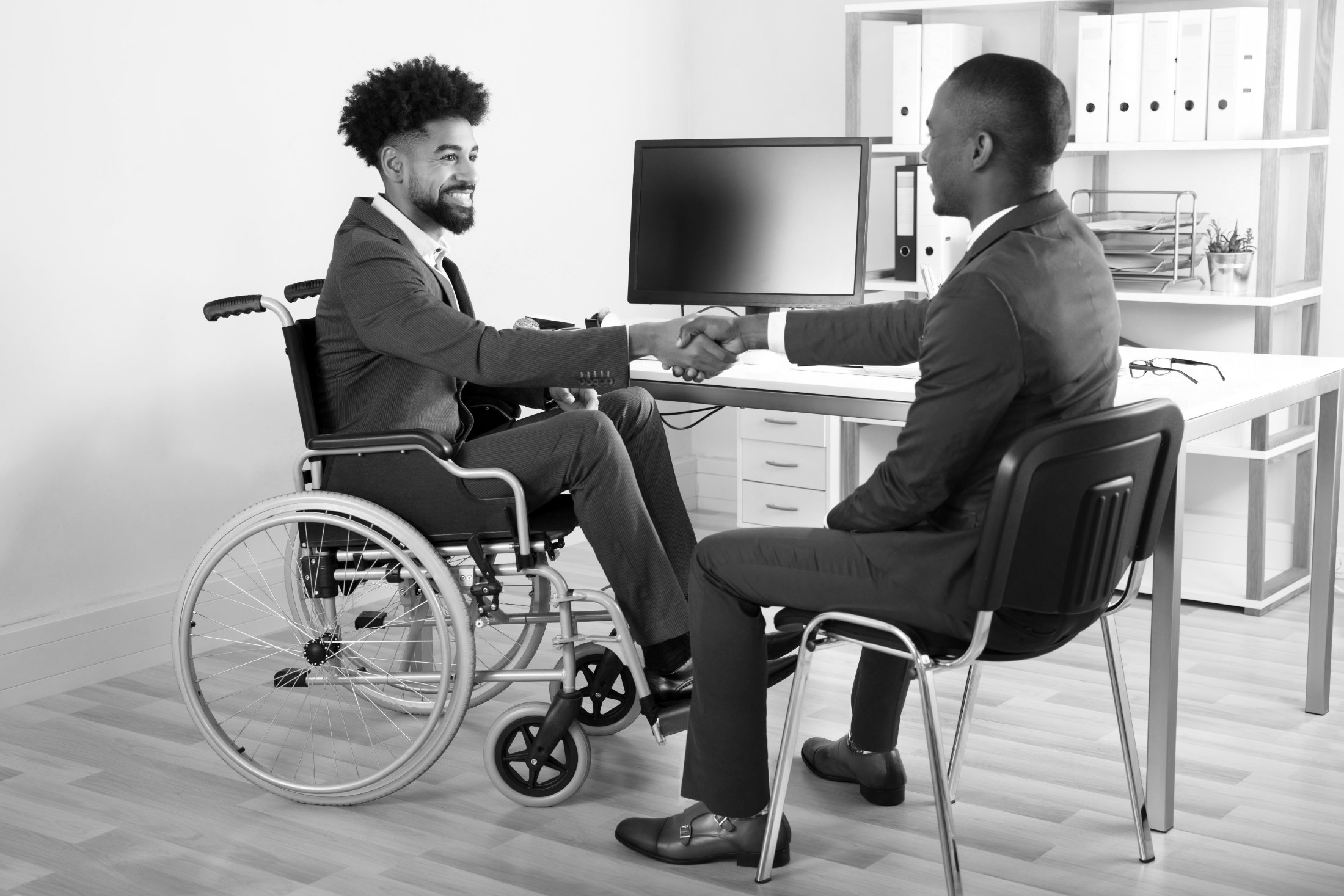 Man in wheelchair shaking hands with sitting man full