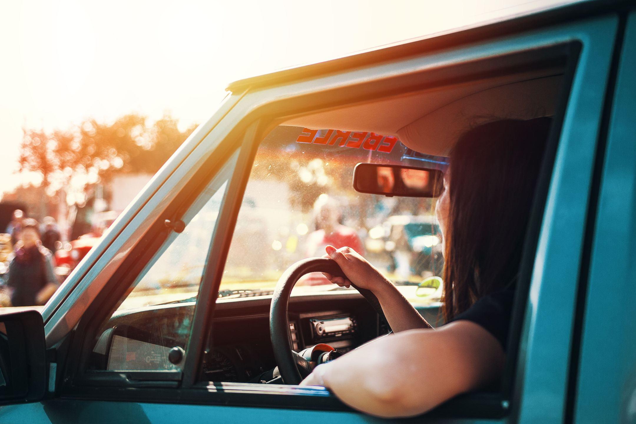 woman in blue car