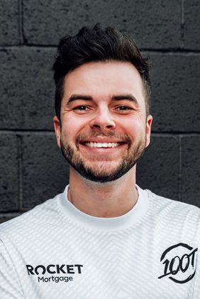 nadeshot smiling in front of brick wall with 100 Thieves jersey