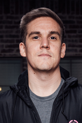 Tyler TeeP standing in front of dark brick wall in black jacket