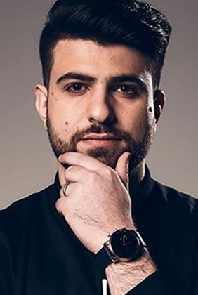 SypherPK in black collared shirt holding chin and showing black watch on wrist
