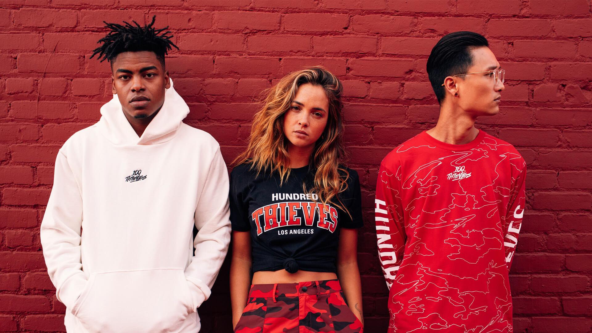 3 models in streetwear pose over brick wall