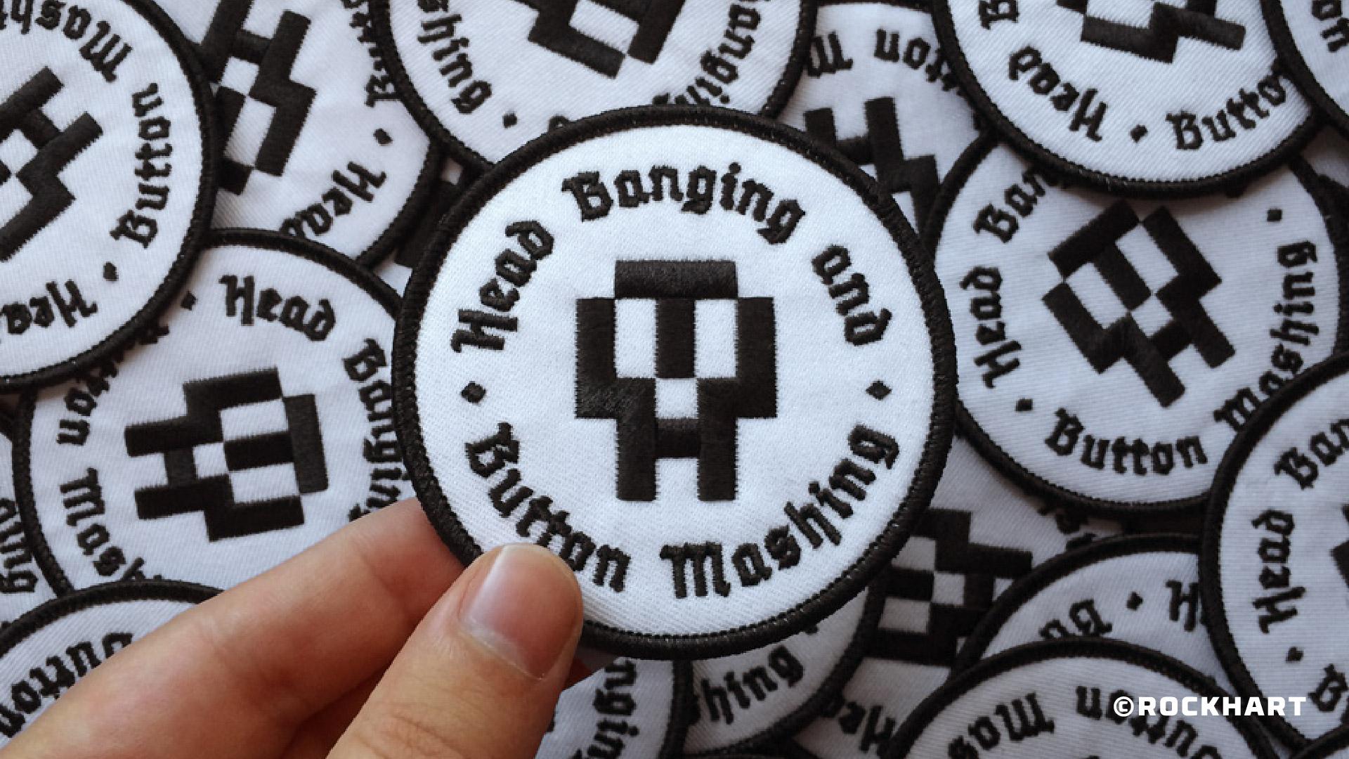 hand holds white black skull badges