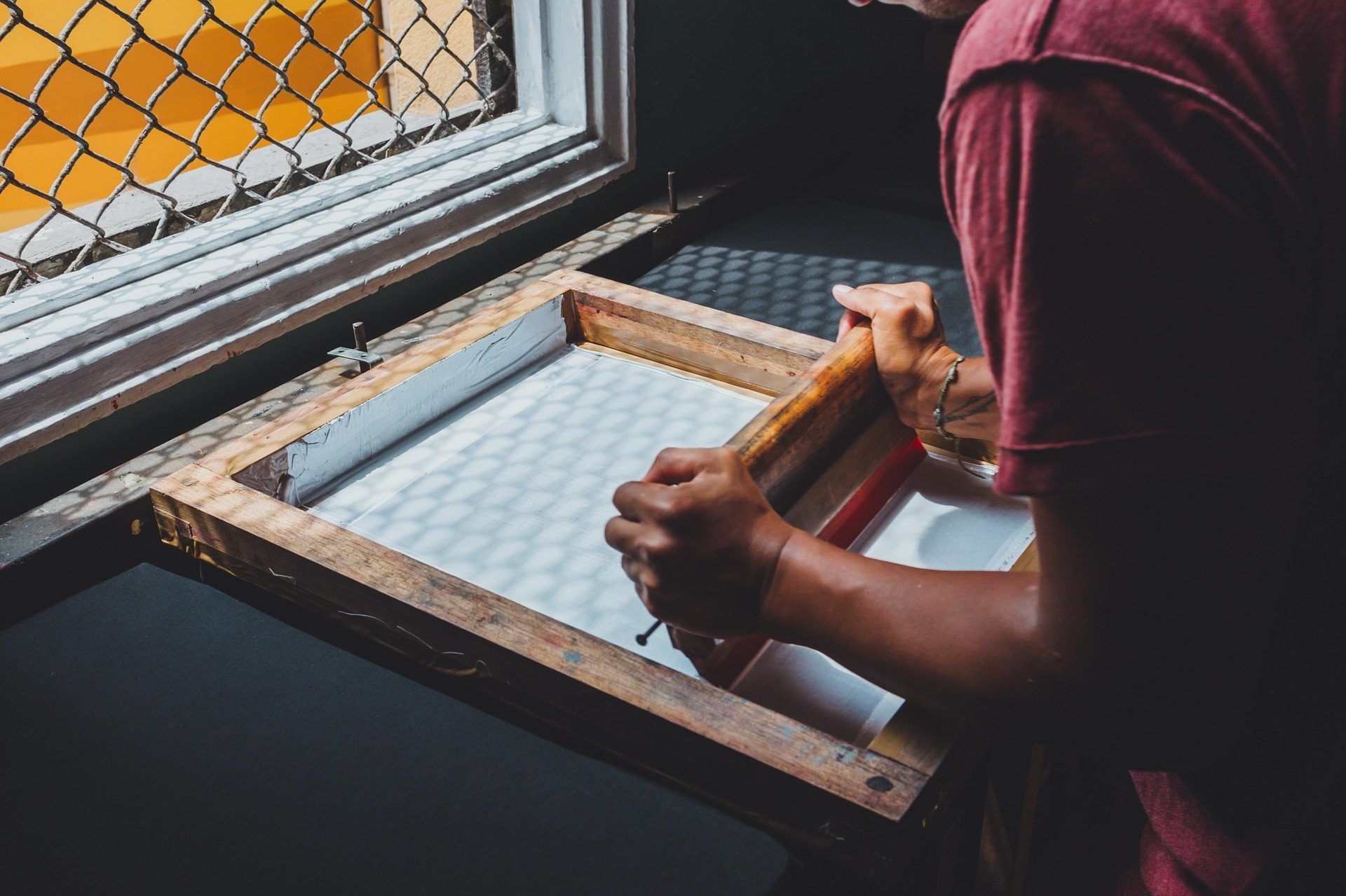 Man Uses Screen Printer by Window