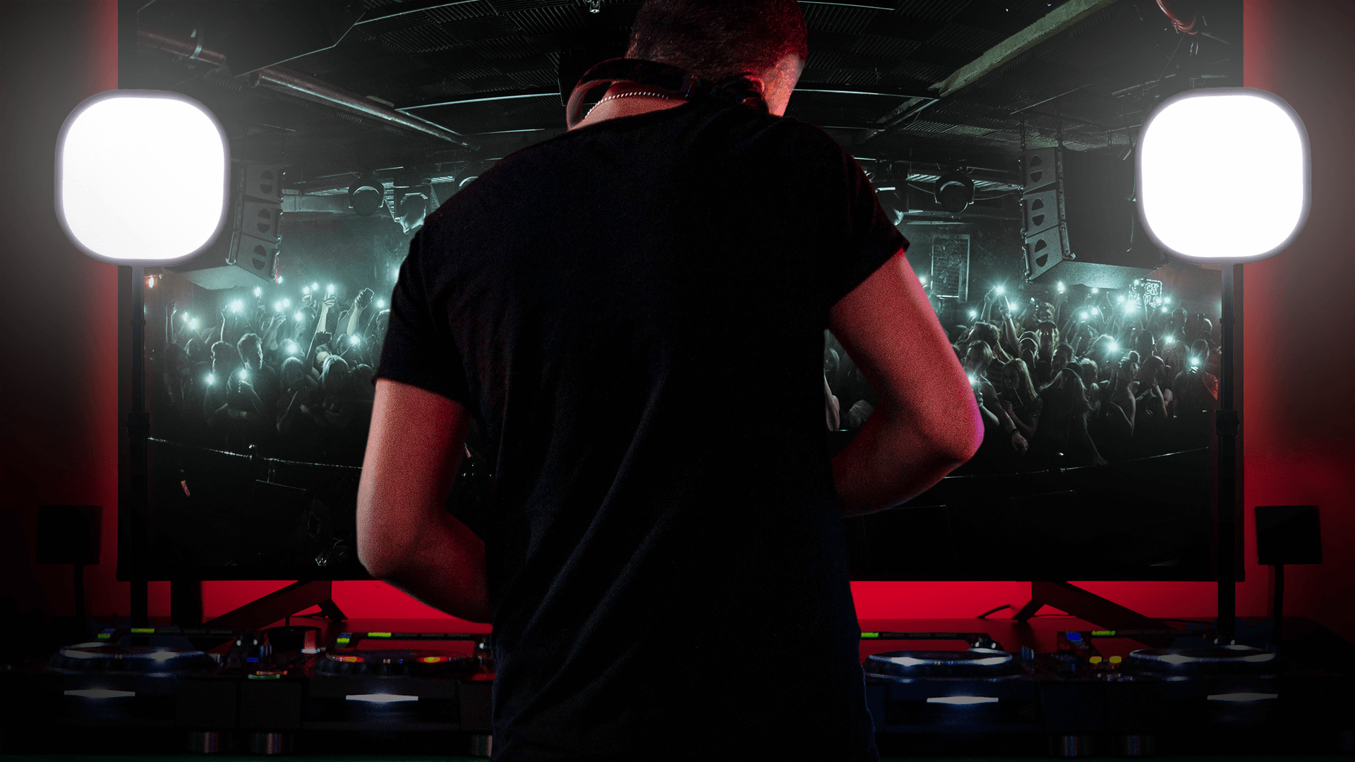 Back profile of DJ standing in front of monitor showing crowd