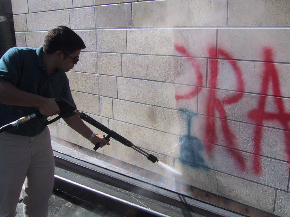 A man power-washes grafitti off a wall