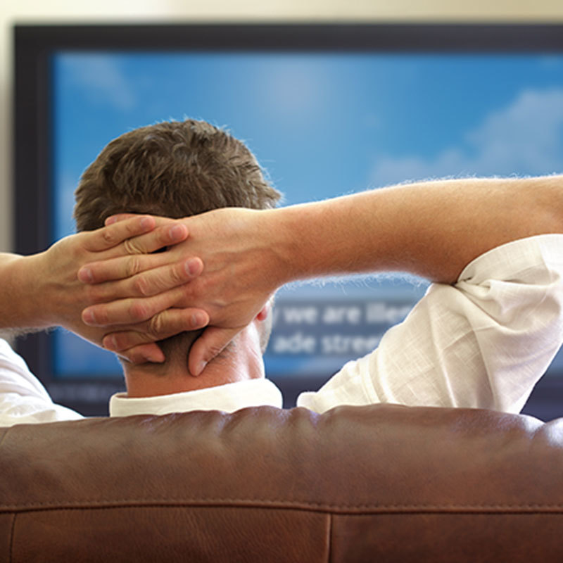 man putting his hands behind his head while watching TV
