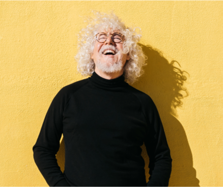 Man laughing black shirt yellow wall testimonials image