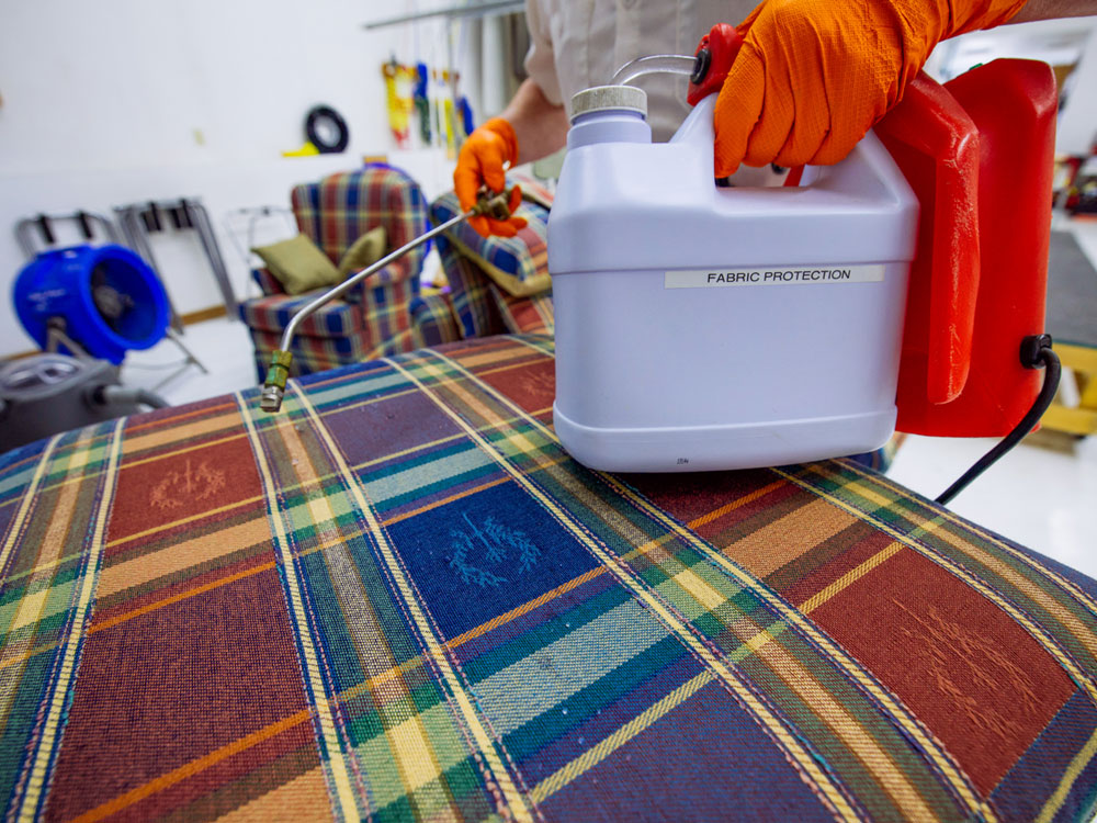 fine fabric care employee applying furniture protectant after cleaning
