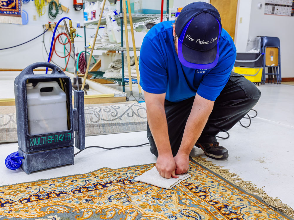 fine fabric care employee performing a color bleed test prior to area rug cleaning