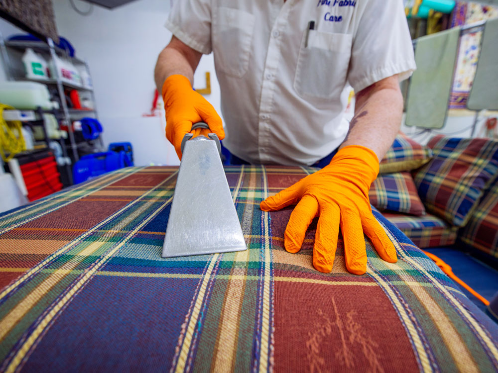 fine fabric care employee cleaning furniture