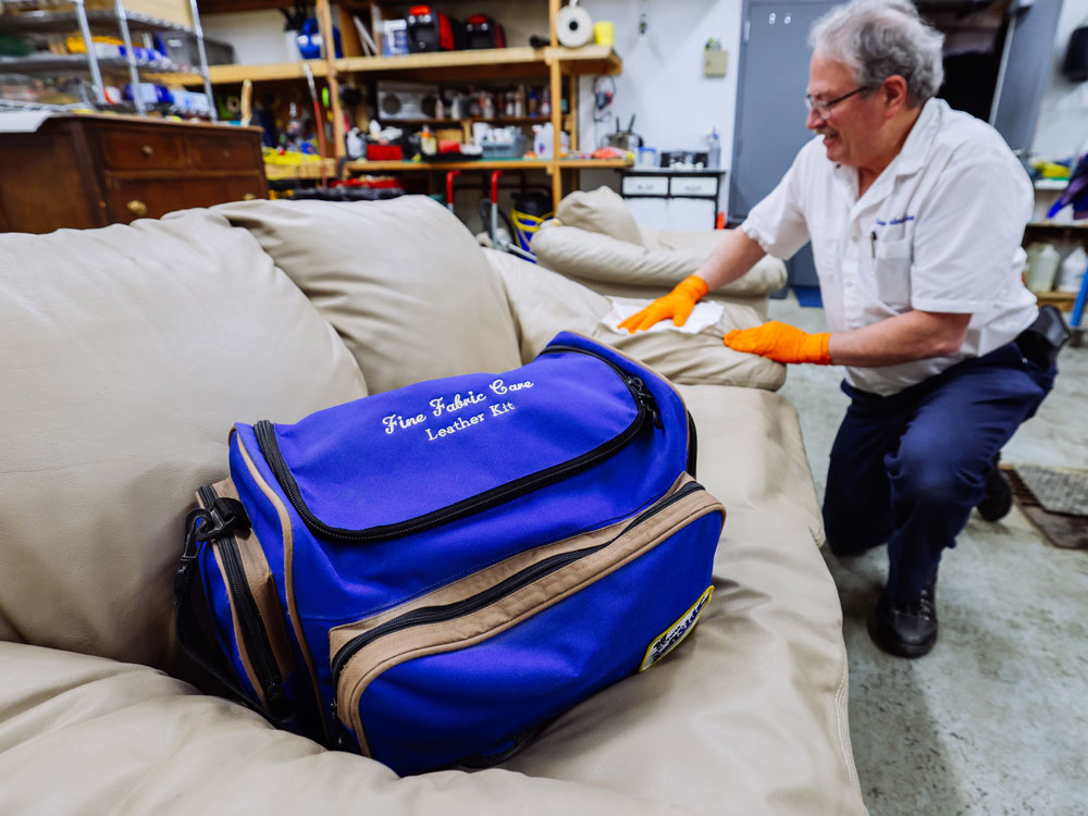 fine fabric care employee cleaning leather couch