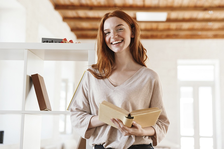 happy-redhead-young-lady-student-reading-book-M5Z7RVC.jpg