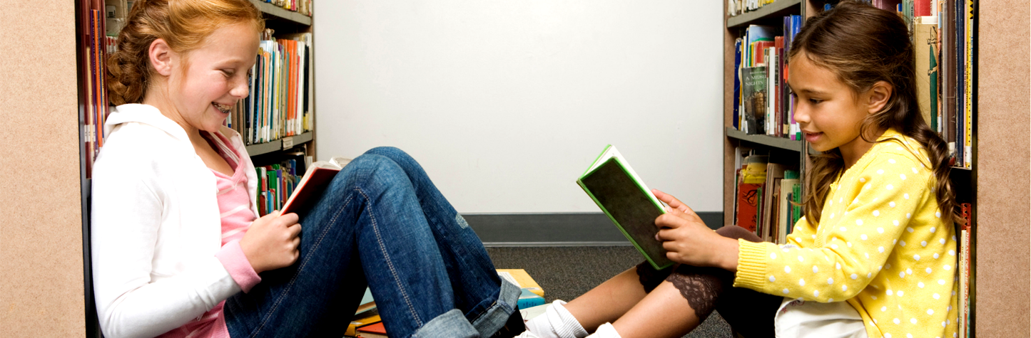 two young girls sitting on the floor in the stacks reading books