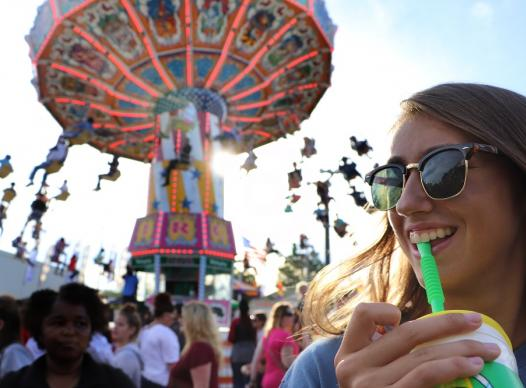 Fair scene with young woman sipping drink.