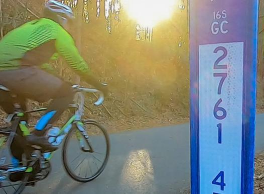 Biker rider near trail marker