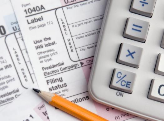 many 1040 tax forms spread on a desk with a pencil and a calculator