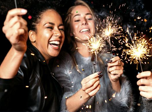 photograph of three young women laughing and holding sparklers