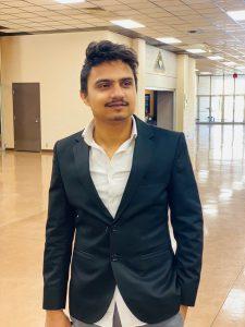 Kaushik Adhikari standing in a hallway.