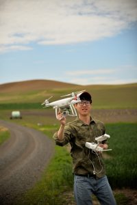 Zhou Tang holding a drone in a field.