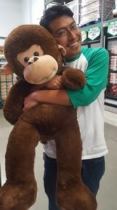 Miguel Rosas holding a large stuffed animal.