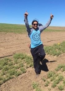Bikash Ghimire jumping in a field.