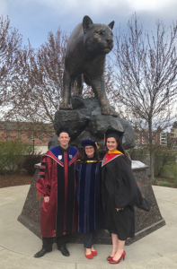 Three people standing in front of the cougar statue.