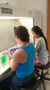 Two people performing lab tests.