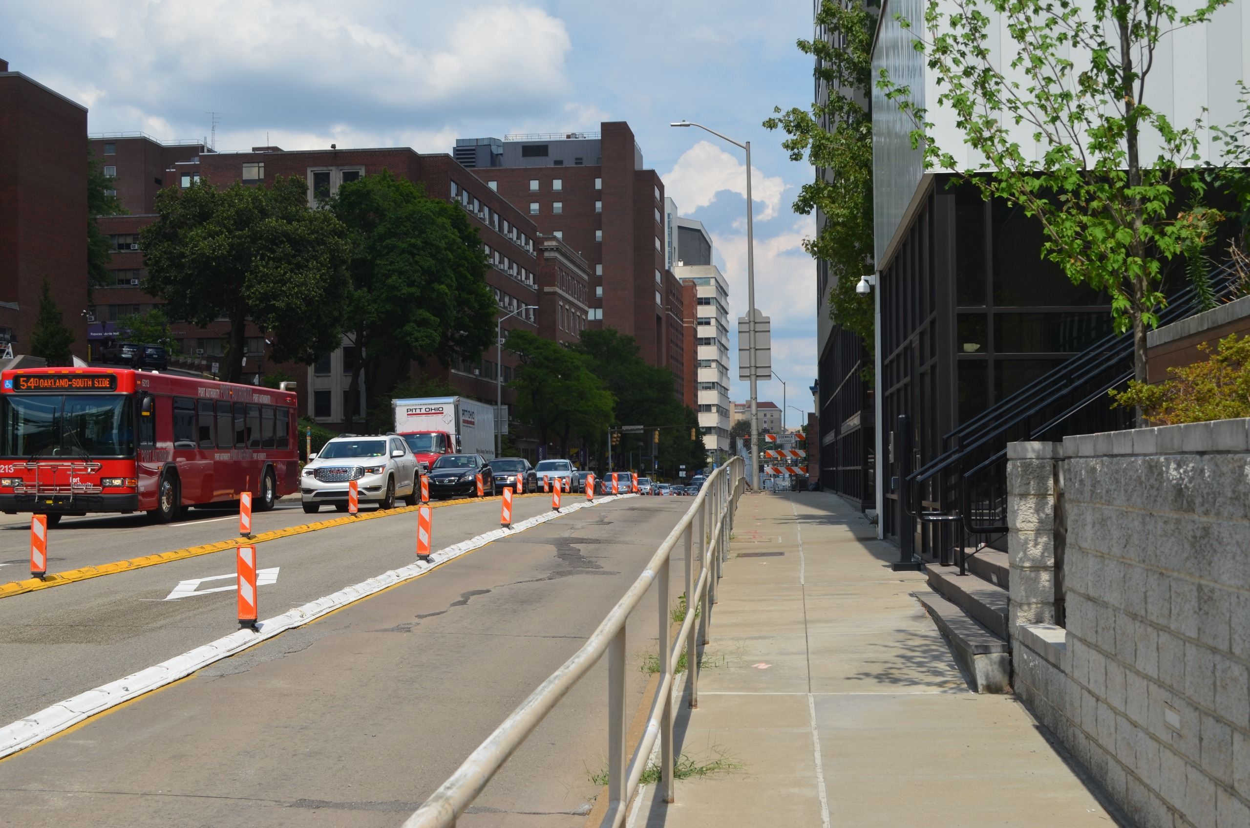 A view across Fifth Avenue showing sidewalk, driving lanes, dedicated busway, and buses.