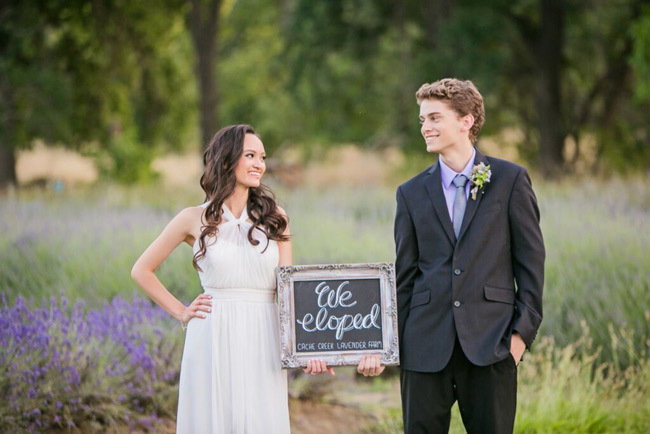 "Newlyweds hold a ""We Eloped"" chalkboard sign 