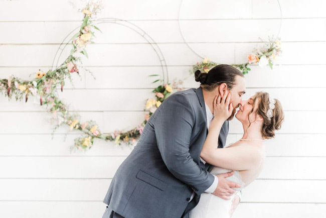 Newlyweds share a kiss in front of floral hoops | Elopement Checklist