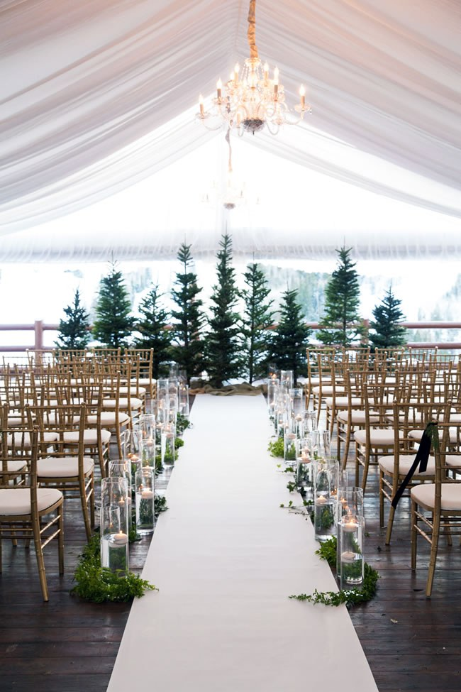A tented winter wedding ceremony with a view of Christmas trees and snow